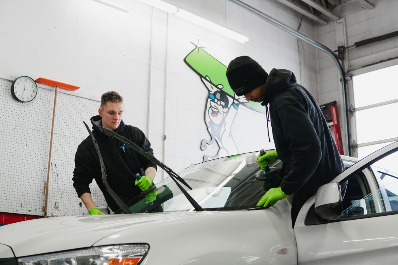 Auto Glass windshield being set into vehicle during replacement